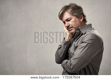 Depressed man having a headache over gray wall background