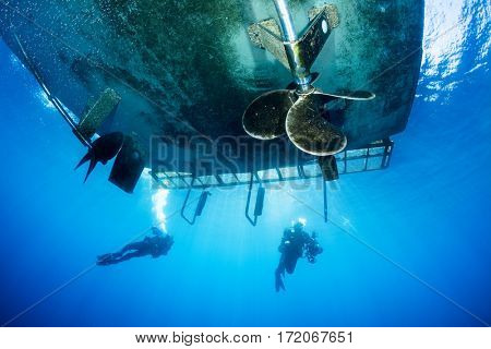 Two scuba divers under a dive boat surfacing after an underwater photography shoot at Catalina Island.