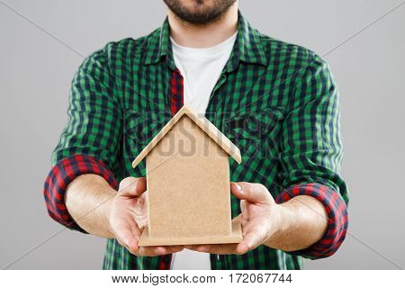 Man in green checked T-shirt holding little wooden house. Mini model of house. Close up, without head. Indoors, studio