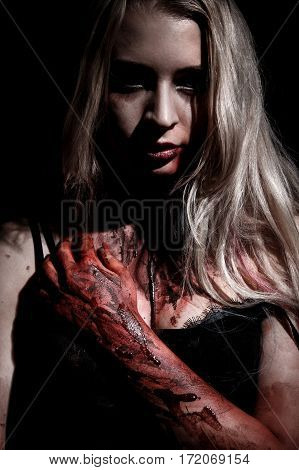 Pale bloody blond woman over black background