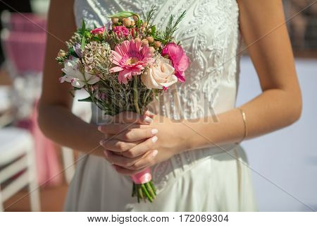 Woman holds small pink bouquet in hands