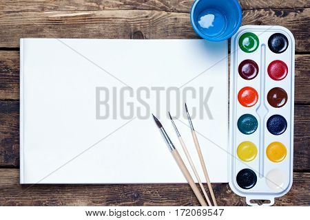 palette of watercolor paints, brushes and cup sheet of blank paper on a wooden surface.top view????