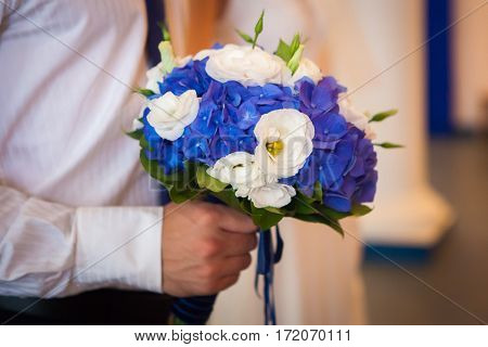 Man waiting for his girlfriend. Close-up of handsome young man in white shirt holding blue bouquet of flowers