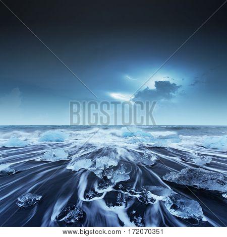 Icebergs floating in Jokulsarlon glacial lake on black volcanic beach. South Iceland. Lightning strike on the cloudy dark sky. Fantastic summer night scene.