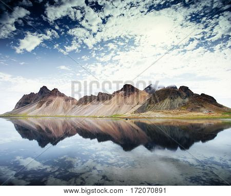 Amazing mountains reflected in the water at sunset. Stoksnes, Iceland.