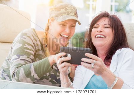 Two Female Friends Laugh While Using A Smart Phone on the Patio.