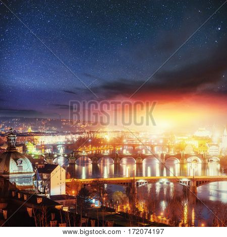 Scenic view of bridges on the Vltava river and of the historical center of Prague: buildings and landmarks of old town with red rooftops. Starry sky.