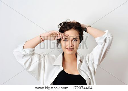 attractive fashion model with blue eyes is posing in shirt on white background