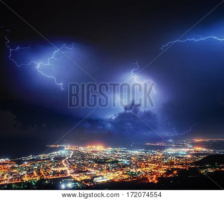 Night lights of the coastal city from the height. Lightning strike on the cloudy dark sky. Fantastic summer night scene.