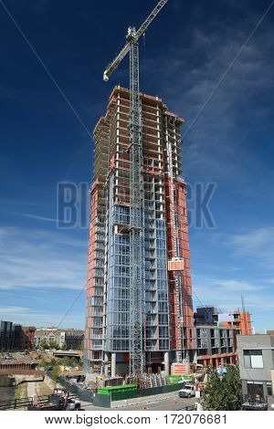 DENVER CO USA - October 8 2016: The Confluence highrise skyscraper under construction in Denver. The luxury residential building located at 2166 15th St. will be 34 stories tall when completed.