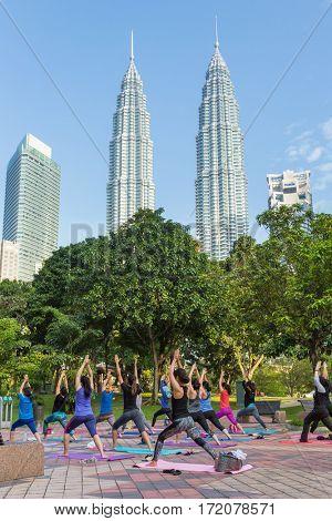 Kuala Lumpur, Malaysia - September 24, 2016: Malaysian women practice yoga in the park with Petronas towers on background in Kuala Lumpur , Malaysia