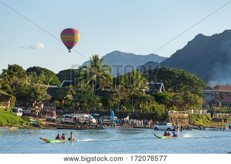 Vang Vieng, Laos - January 19, 2017: Unidentified tourists are riding  speedboats in Vang Vieng village with a hot air balloon on background.