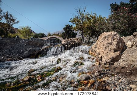 Small waterfall and old arch on a background in Preveli, Crete island