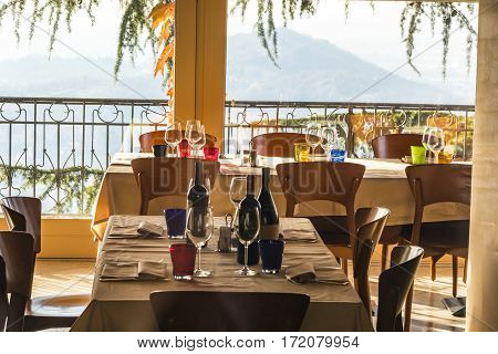 Tables in italian restaurant served with a bottle of wine and wine glasses