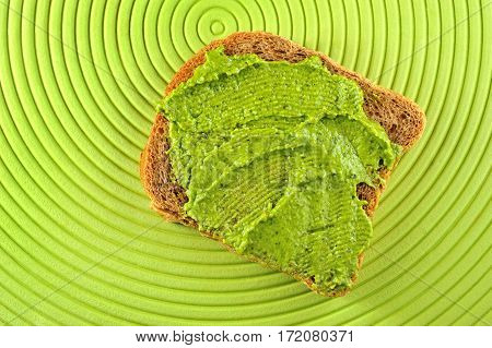 whole grain bread with fresh basil pesto on green background