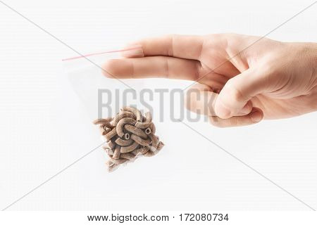 Hand holding Plastic transparent zipper bag with half wholegrain raw pasta isolated on white, Vacuum package mockup with red clip. Concept