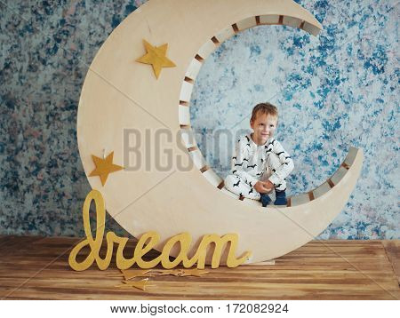 Child in soft and warm pajamas lying on a wooden months with stars in the studio
