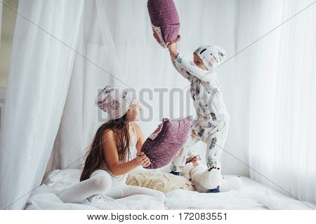 Children in soft warm pajamas playing in bed