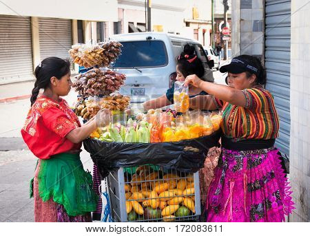 GUATEMALA CITY, GUATEMALA-DEC 25, 2015: Mayan women sell   Guatemalan food and fruits at the street of Guatemala city on Dec 25 2015. Guatemala.