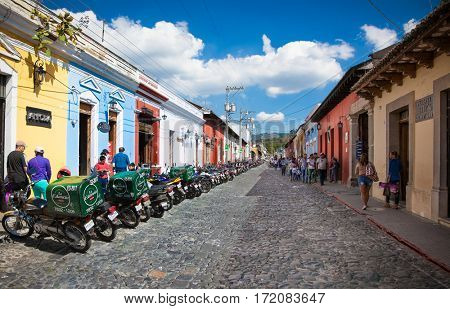ANTIGUA, GUATEMALA-DEC 27, 2015: Main street with local people and colonial houses in Antigua on Dec 27, 2015. Guatemala.  The historic city Antigua is UNESCO World Heritage Site since 1979.