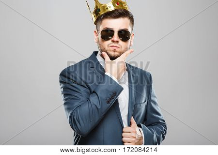 Stylish young man in suit with bow and sunglasses. Wearing crown. Thinking about something, thoughtful, touching chin. Outrageous, fancy look. Waist up, studio, indoors