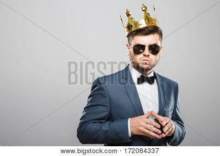 Angry man in suit with bow and sunglasses. Wearing crown. Hands together, annoyed face. Outrageous, fancy look. Waist up, studio, indoors