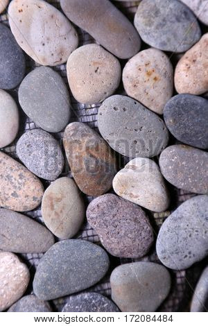 river rock. river rock construction tile. close up of floor or wall tile made of smooth stones. construction materials.