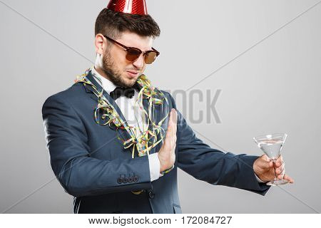 Man in suit with bow and sunglasses. Don't want martini, disguise. B-day hat, confetti. Outrageous, fancy look, cool. Waist up, studio, indoors