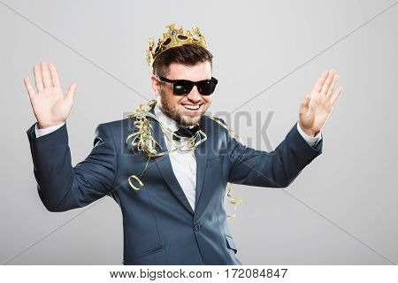 Stylish young man in suit with bow and sunglasses. Wearing crown, confetti on shoulders. Having fun, hands up, smiling. Outrageous, fancy look, eccentric. Waist up, studio, indoors