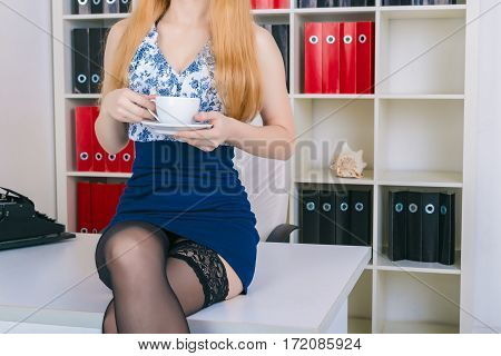 Sexy woman in a black stockings on the office table with coffee. Beautiful businesswoman portrait in miniskirt.