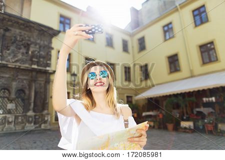 Cute tourist girl with light hair and red lips wearing hat and glasses, holding map and making selfie at old European city background and smiling, sunny weather.
