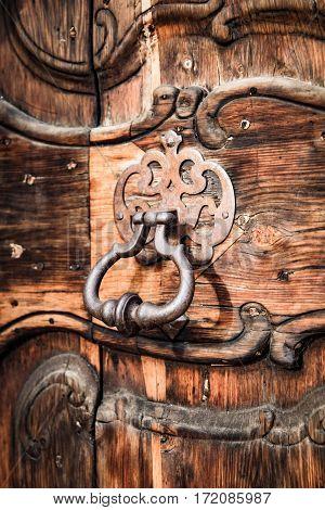 Ancient door knocker of a medieval wooden portal.