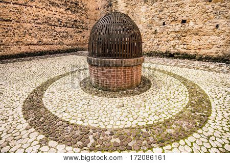 Medieval well covered by an iron grate.