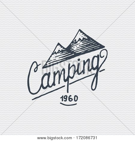 vintage old logo or badge, label engraved and old hand drawn style with lettering camping and mountains.
