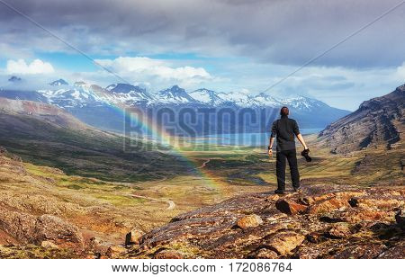 Fantastic views of the mountains and a little rain and a rainbow in Iceland. Colorful colors. Dramatic cumulus clouds. The man considers beautiful landscapes. Europe.