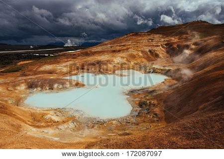 Giant volcano overlooks. Turquoise provides a warm geothermal water. Iceland.