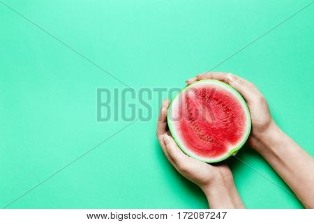 Half of Sweet Mini Watermelon in Female Hands with Green Copy Space.