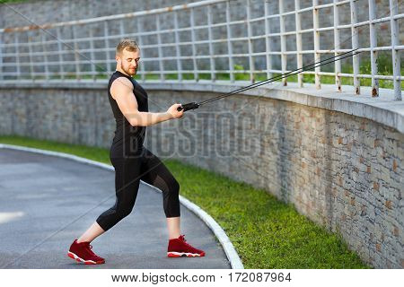 Man training with expander hooked on fence. Muscular sportsman pulling expander to himself and looking down, one leg ahead. Sport, outdoors, stadium, full body