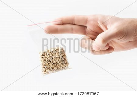 Hand holding Plastic transparent zipper bag with half Oatmeal raw flakes isolated on white, Vacuum package mockup with red clip. Concept