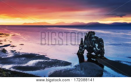 Hvitserkur is a spectacular rock in the sea on the Northern coast of Iceland. Legends say it is a petrified troll. On this photo Hvitserkur reflects in the sea water after the midnight sunset.