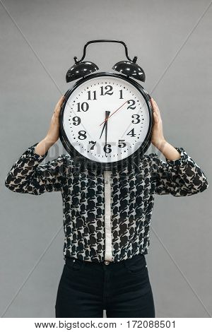 The girl holding a very large alarm clock. Time goes by quickly on such a big clock