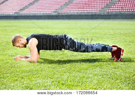Man standing in plank position on grass. Muscular sportsman leaning on hands, horizontal position. Full body, profile, outdoors, stadium