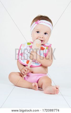 Little girl surprised with a spoon isolated on white background