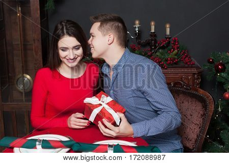 Young man gives a gift to beautiful woman