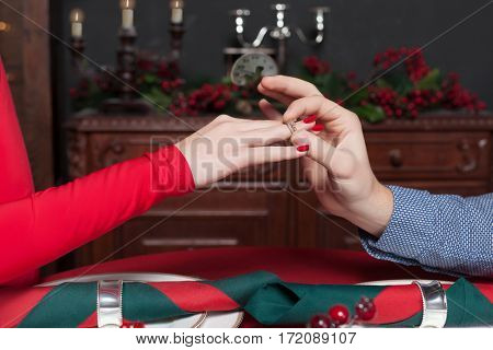 Man puts a wedding ring on womans hand closeup