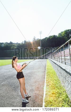 Sport, exercises with training loop outdoors. Profile of sporty girl in rose top and black shorts doing exercises with training loop on stadium. Full body, profile, sunlight