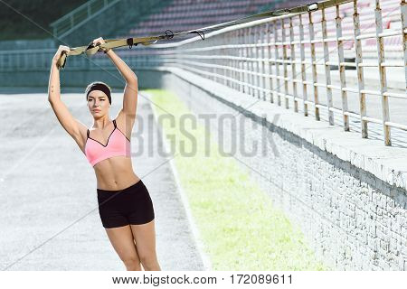 Sport, exercises with training loop outdoors. Girl in rose top and black shorts doing exercises with training loop on stadium. Sporty girl in good shape with hands up, looking aside