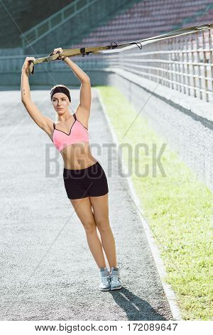 Sport, exercises with training loop outdoors. Girl in rose top and black shorts doing exercises with training loop on stadium. Sporty girl in good shape with hands up, looking aside, full body