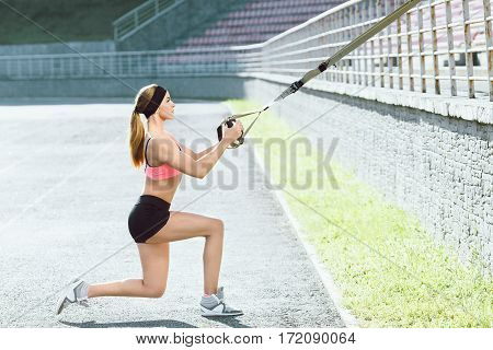 Sport, exercises with training loop outdoors. Profile of girl in rose top and back shorts doing exercises with training loop on stadium. Sporty girl in good shape squatting on one leg, full body