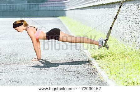 Sport, exercises with training loop outdoors. Profile of girl in rose top and black shorts doing exercises with training loop on stadium. Sporty girl standing on hands, full body